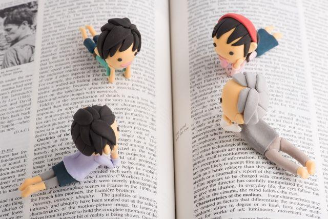 本の上でくつろぐ家族(人形)