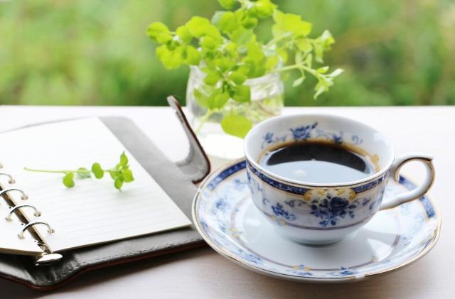 ノートとカップのコーヒー