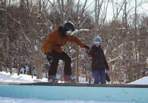 snowboarder learning boardslide on box at freestyle camp