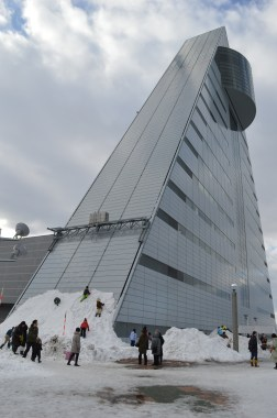 Children building their own snow bank to slide down the side of the triangular ASPAM building