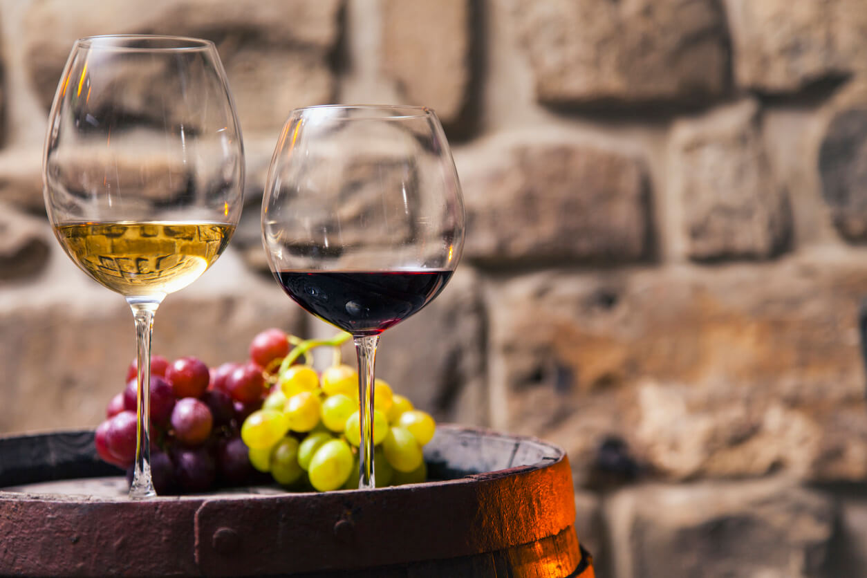 red and white wine glasses with grapes against a stone wall