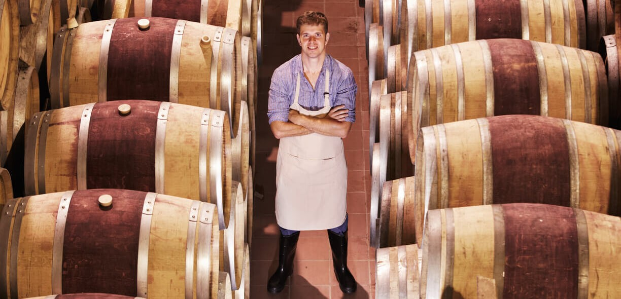 Wine Barrel Cleaning & Preparation- man standing between a row stored wine barrels