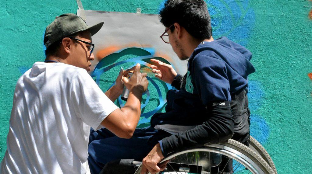Voluntario pinta un mural junto con beneficiario