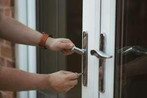 Pessoa colocando a chave na fechadura para abertura da porta de entrada.