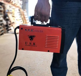 Imagem composta por uma pessoa segurando a máquina de solda MMA 244 da USK com uma mão, mostrando sua leveza e praticidade.