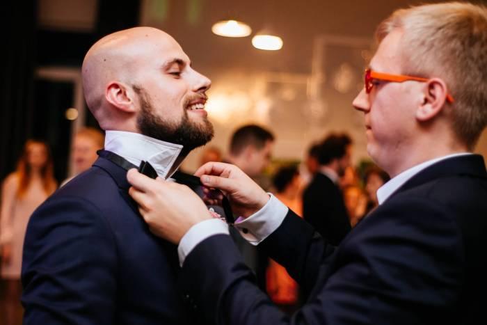 """Poradnik ślubny - co to są oczepiny w czasie wesela: pan młody zakłada swoją muchę """"przyszłemu panu młodemu"""""""