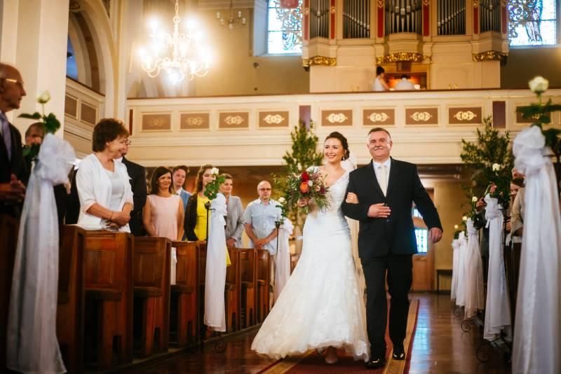 Przebieg ślubu kościelnego - wprowadzenie Panny Młodej przez jej ojca. Zdjęcia wykonane w Kościerzynie w województwie Pomorskim, w trakcie ślubu kościelnego. Ojciec prowadzi Pannę Młodą do ołtarza.