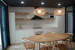 Cocina moderna con línea blanca y madera en Apartamento Lapamán