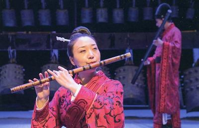 Musician playing replica of ancient instruments.