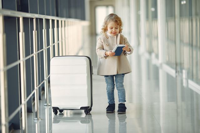 little girl in airport with cabin bag