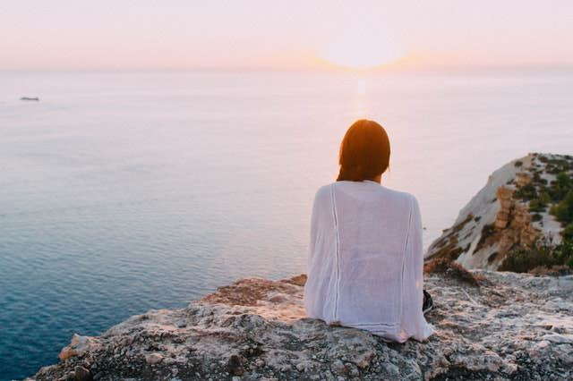 woman watching ocean and sunset from cliff
