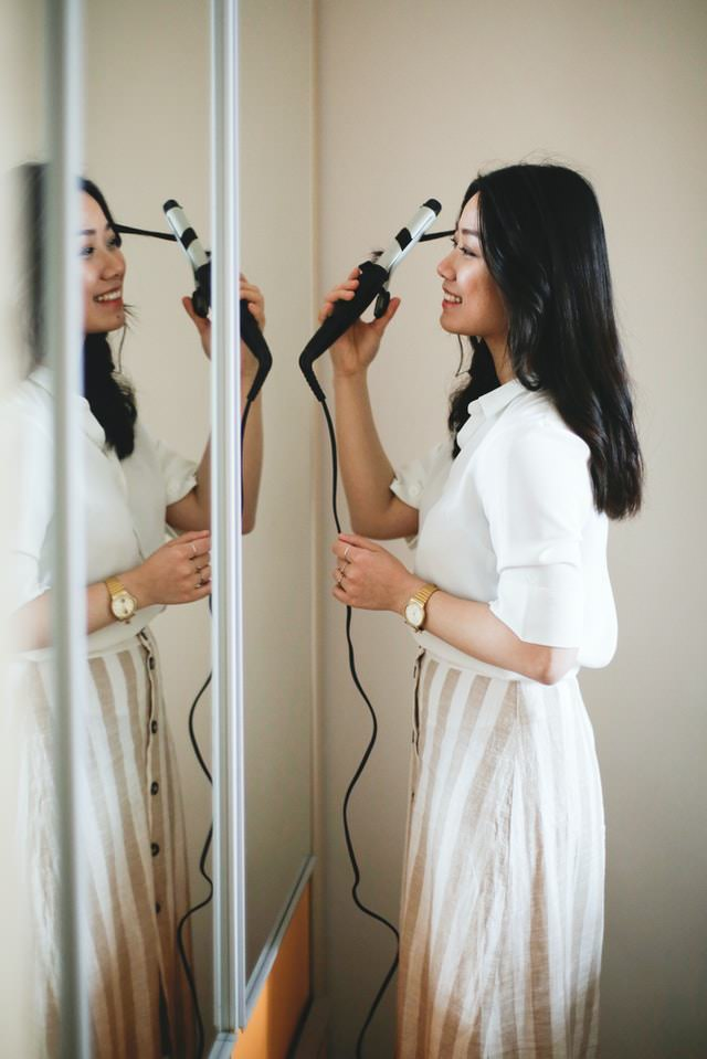 woman using curling iron in front of mirror