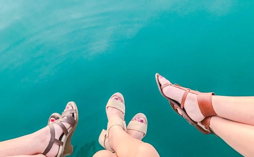 three women wearing flip flops over blue ocean water.