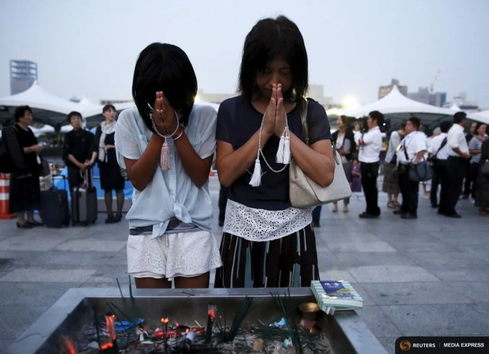A mother and her daughter pray for the atomic bomb victims in front of the cenotaph for the victims of the 1945 atomic bombing, at Peace Memorial Park in Hiroshima, western Japan, August 6, 2015, on the 70th anniversary of the world's first atomic bombing of the city.  REUTERS/Toru Hanai