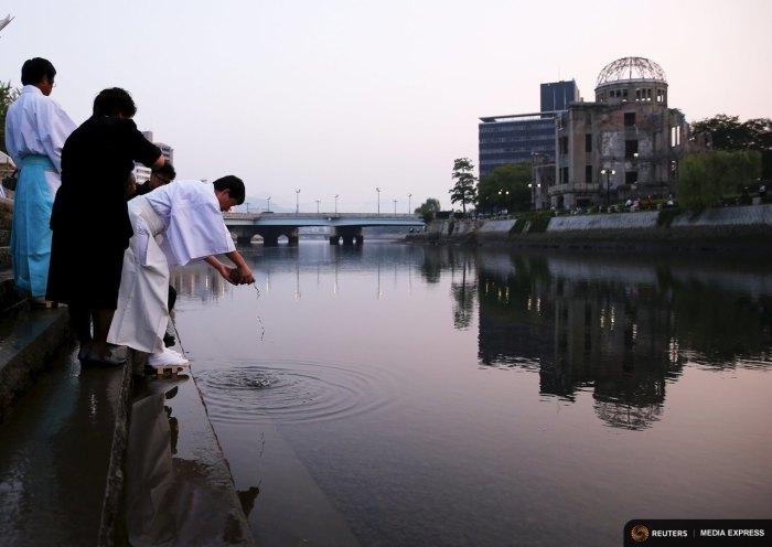 A Shinto priest pours sake into the Motoyasu River during prayers opposite the Atomic Bomb Dome at sunrise in Hiroshima, western Japan, August 6, 2015.  REUTERS/Thomas Peter