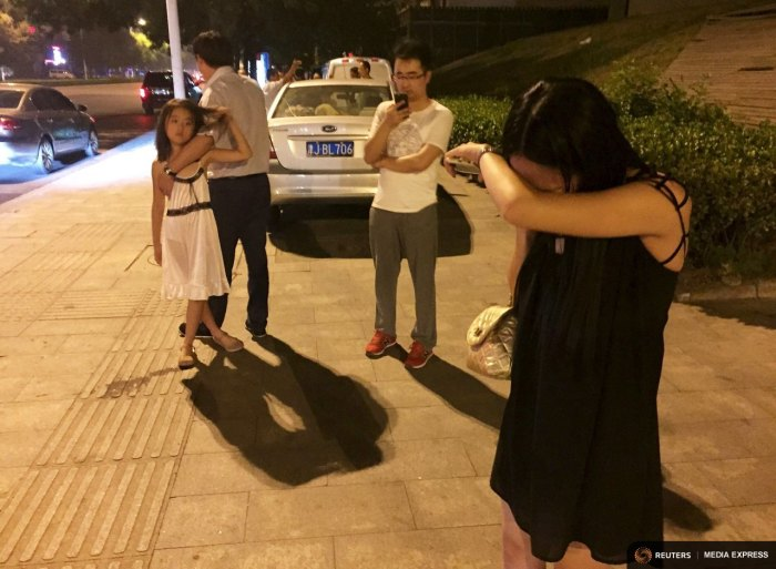 People react near a street after a blast at Binhai new district, in Tianjin municipality, China, August 12, 2015. REUTERS/Stringer