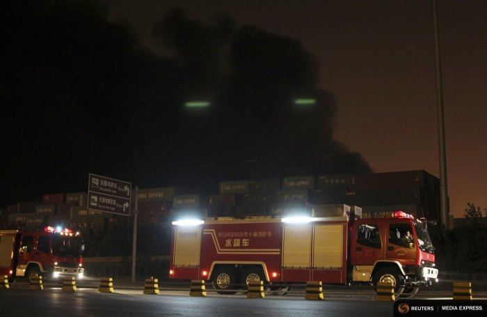 Firefighter's trucks are pictured in front of heavy smoke rising behind shipping containers after blasts at Binhai new district in Tianjin municipality, China, August 13, 2015. REUTERS/Stringer