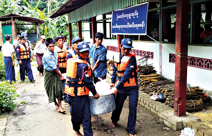 Responders bring relief supplies to people evacuated due to riverine flooding during an emergency simulation in Toungoo township in Myanmar.