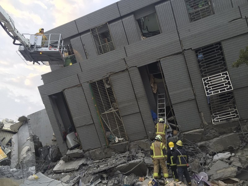 Rescue personnel work at a damaged building after an earthquake in Tainan, southern Taiwan, February 6, 2016. REUTERS/Pichi Chuang