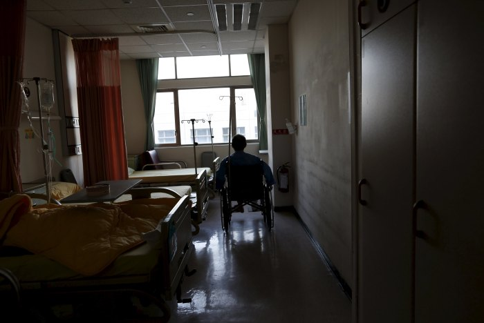 Wu na-rong, a 63 year-old security guard of the 17-storey apartment building which collapsed after an earthquake, sits on a wheelchair in a hospital after fracturing his lower leg during the disaster in Tainan, southern Taiwan, February 8, 2016. REUTERS/Tyrone Siu