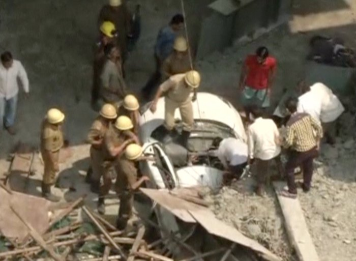Rescue workers attempt to rescue a person trapped in a car after a flyover collapsed, in Kolkata, India, in this still image taken from video March 31, 2016. REUTERS/ANI via Reuters TV