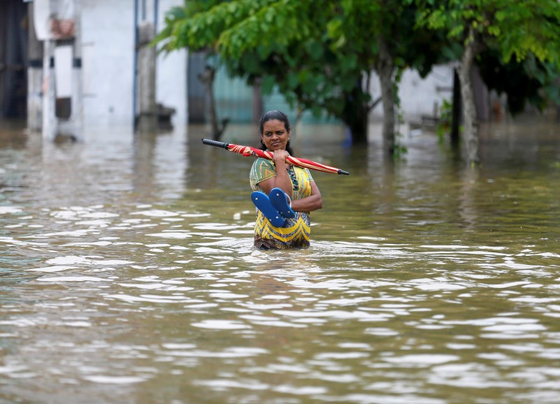 A woman stands on a flooded road in Biyagama, Sri Lanka May 17, 2016. REUTERS/Dinuka Liyanawatte