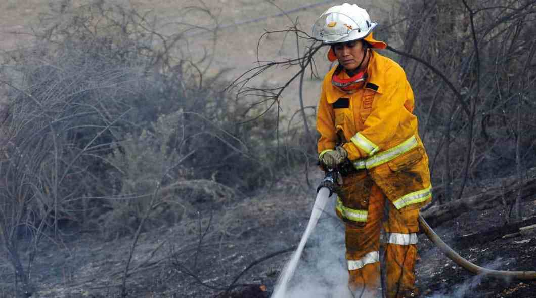 A rural female firefighter mopping up after a bushfire. WAFA promotes firefighting as a viable career or volunteer choice for women.
