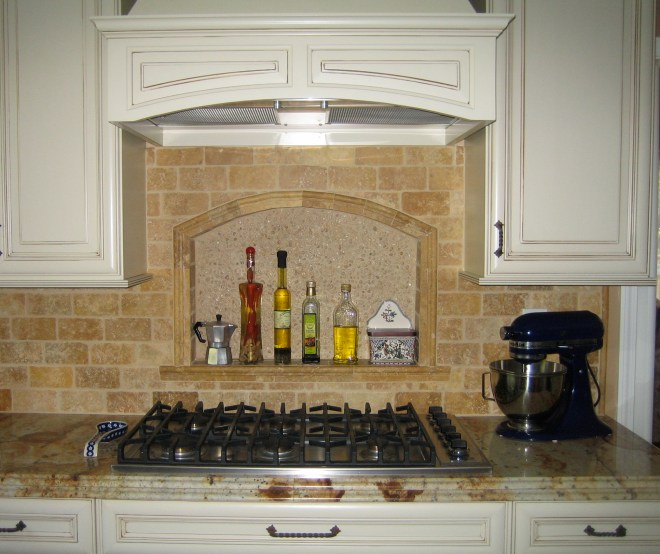 Tumbled travertine backsplash with niche over cooktop.
