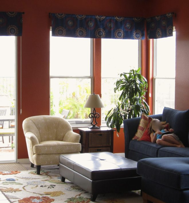 Custom window valances help unify the colors of the walls and furnishings in this family room.