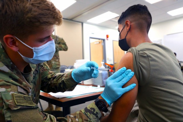 Spc. Tyler Boyer, a Hayden, Colorado native and medical specialist assigned to the 1st Stryker Brigade Combat Team, 4th  Infantry Division, administers the COVID-19 vaccine at Fort Carson, Colorado Aug 3, 2021. The 4th Inf. Div. remains committed to keeping the Fort Carson community safe and healthy by offering mobile vaccinations centers.  (U.S. Army photo by Sgt. Andrew Greenwood)