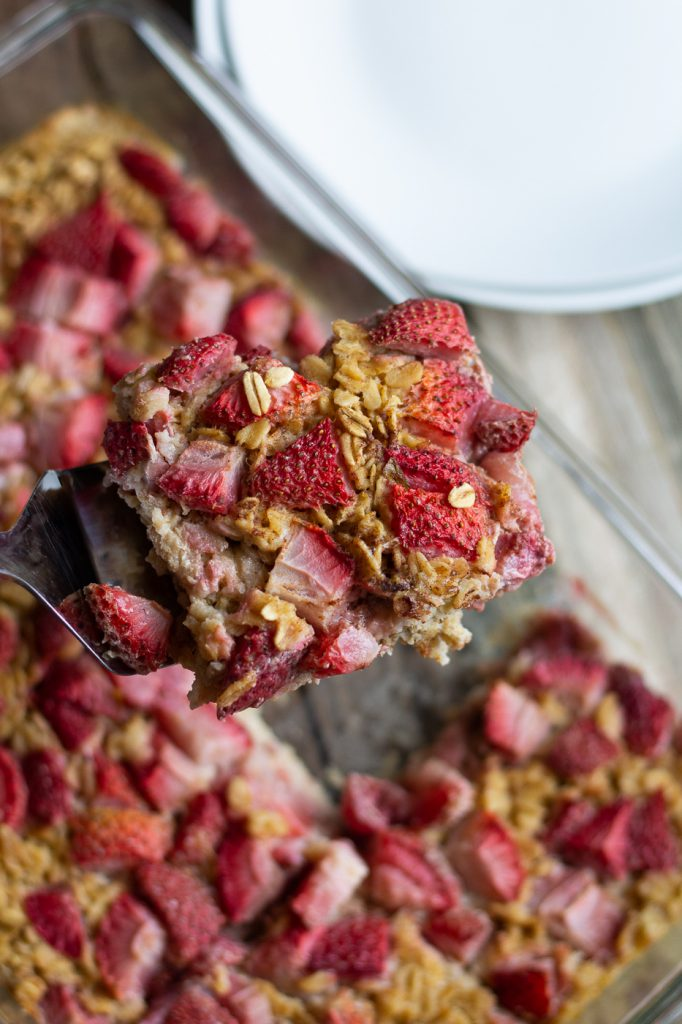 Slice of healthy strawberry baked oatmeal on a spatula