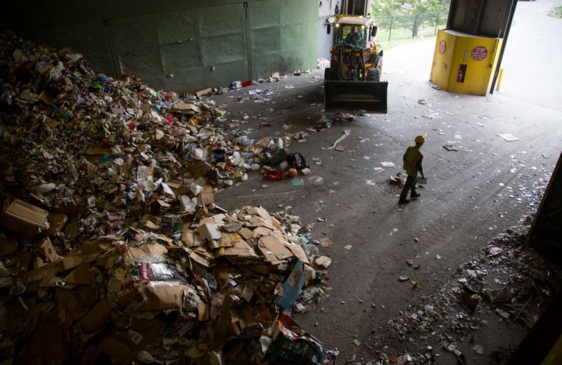 Recycling material is pushed into mounds before being sorted at an Ecomaine facility on Thursday, May 3, 2018.