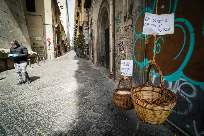 Solidarity basket with a note that read 'Who can lay, who cannot take' on one of the deserted streets in the historic center of Naples, southern Italy, on March 30, 2020.