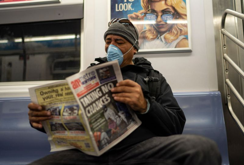 A passenger wearing a surgical mask a daily newspaper while riding an uptown subway in New York City on March 18, 2020.