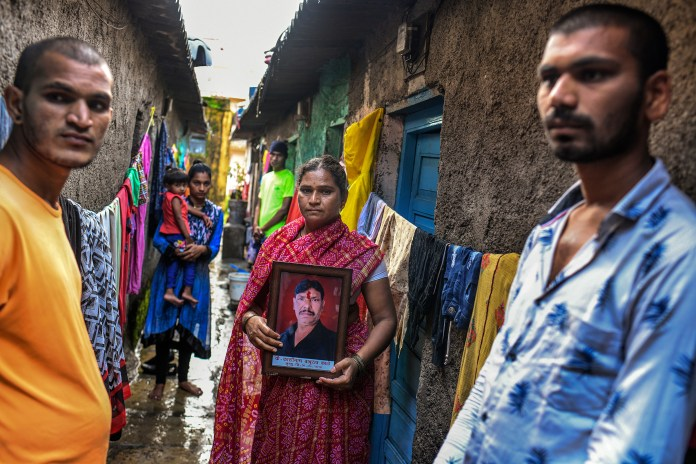 Kashinath Kale's widow, Sangeeta, flanked by her sons Akshay, left, and Avinash, holds a framed portrait of her late husband outside their home in Kalewadi, a suburb of Pune. Kale, 44, died from COVID-19 in July as the family desperately tried to find a hospital bed with a ventilator.