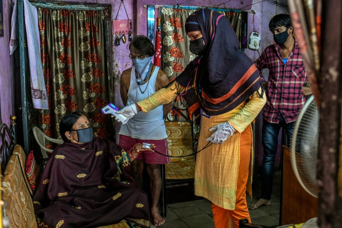 A health care worker checks a woman's temperature and oxygen saturation in the Dhole Patil slum on Aug. 10.