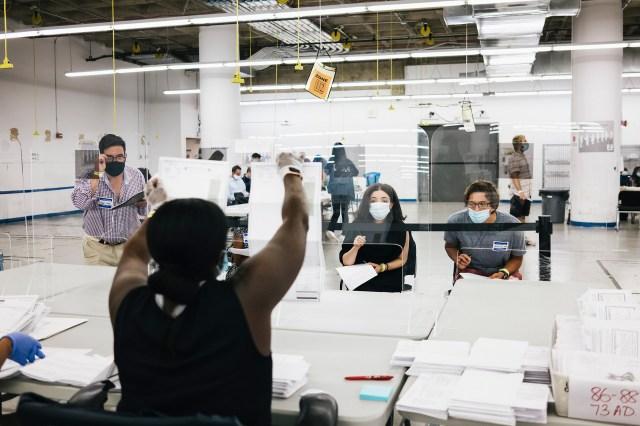 Los voluntarios de la campaña observan cómo un funcionario electoral muestra una boleta por correo en Manhattan
