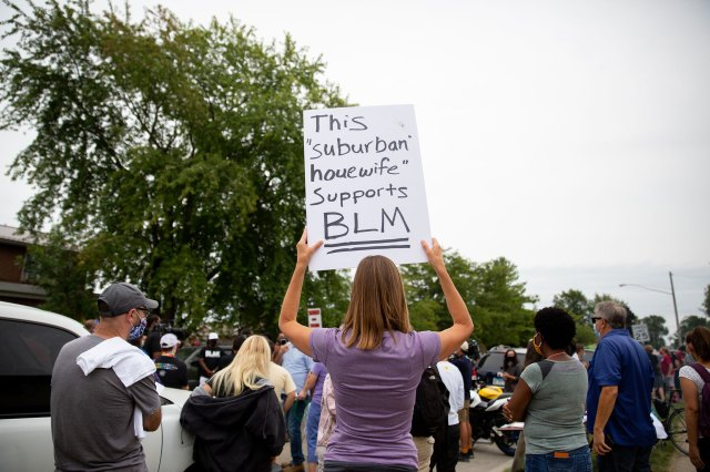 A supporter of Jacob Blake's family holds a sign up at a peaceful gathering near the site where Blake was shot by police in Kenosha, Wis., on Tuesday Sept. 1, 2020.