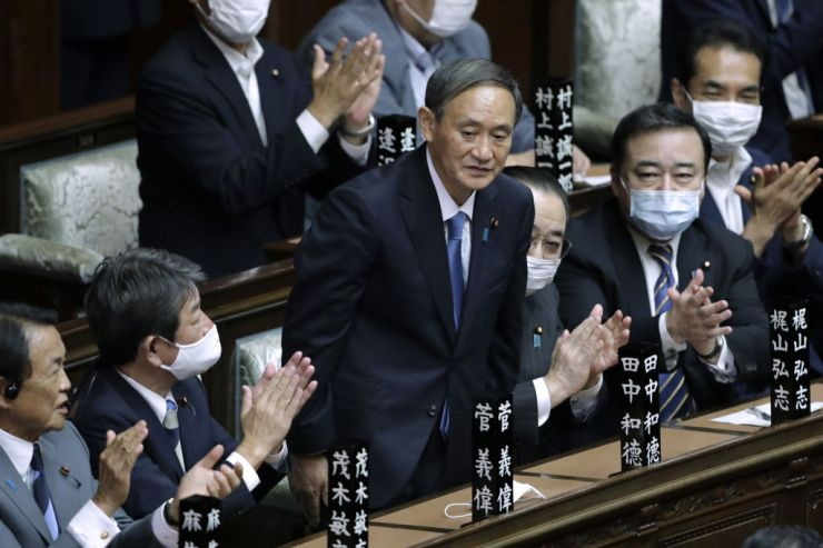 Yoshihide Suga, president of the Liberal Democratic Party (LDP), middle, receives a round of applause after being elected as Japan's prime minister during an extraordinary session at the lower house of parliament in Tokyo, Japan, on Sept. 16, 2020.