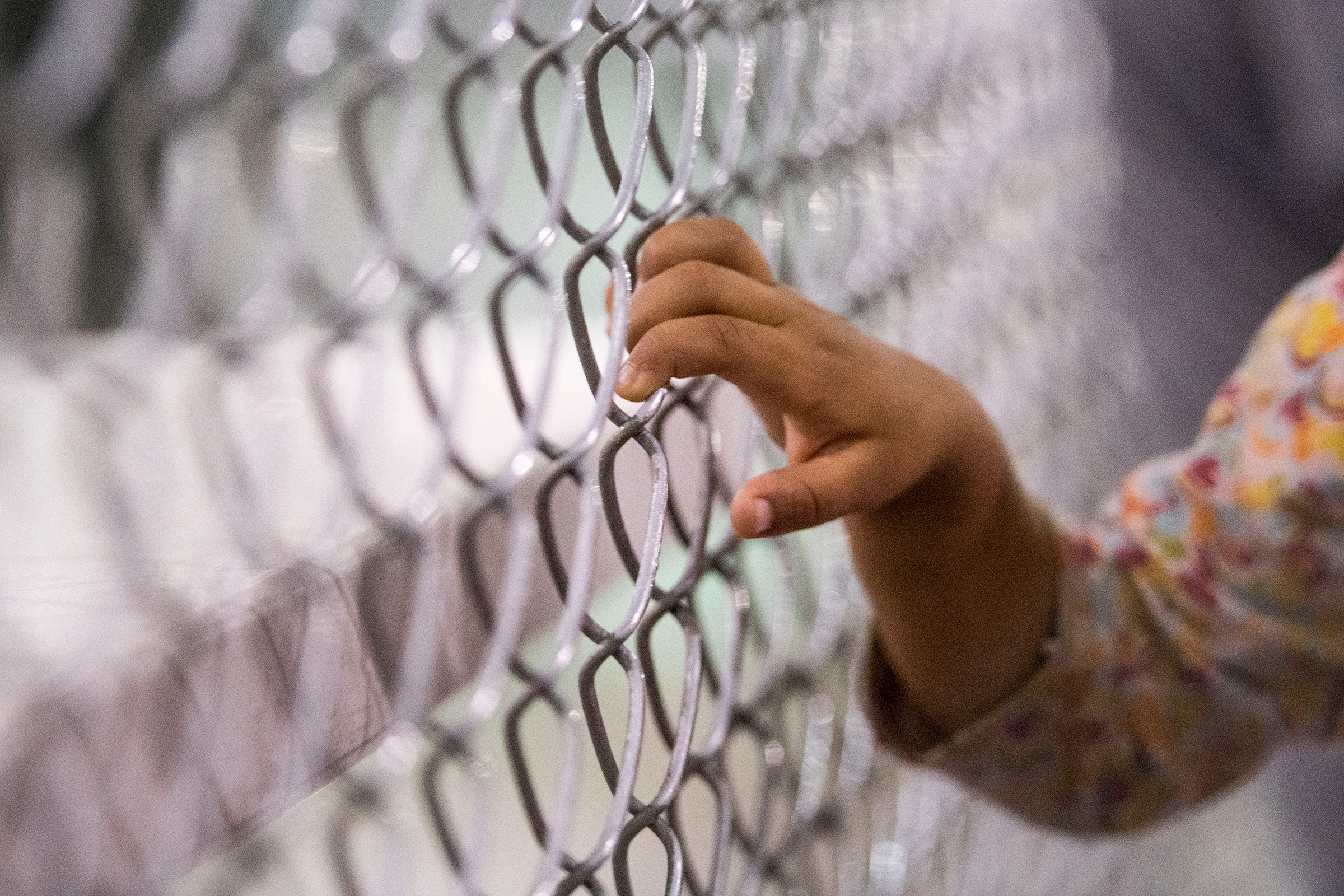 A child holds onto a fence in the U.S. Border Patrol Central Processing Center in McAllen, Texas, on Aug. 12, 2019.