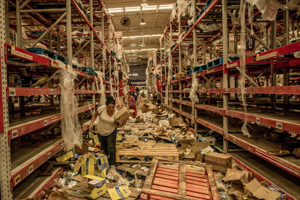 People look through the remains of a looted supermarket in Santiago, Chile, Oct. 23, 2019. (Tomas Munita/The New York Times)