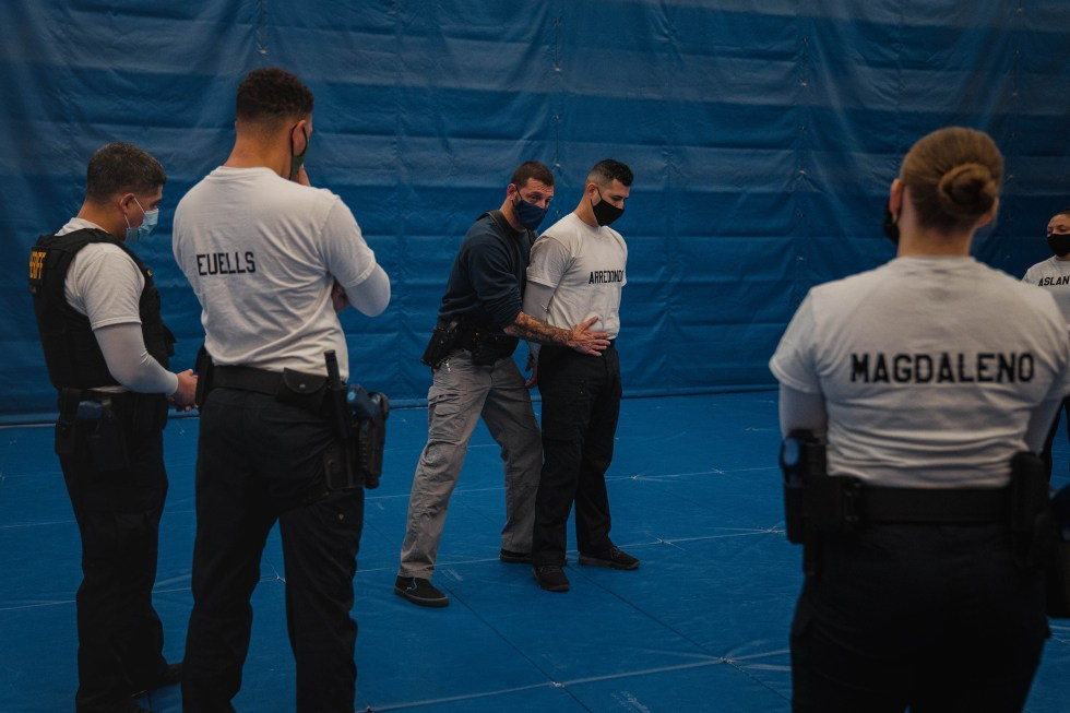 Instructor Javier Sola teaches frisking and handcuffing methods to police recruits.