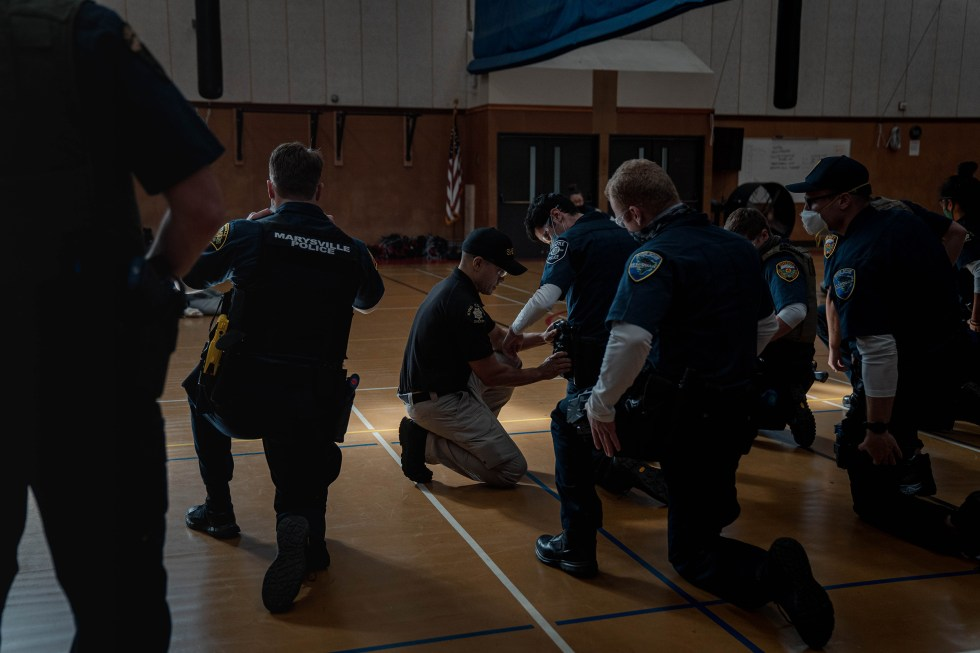 Police recruits practice holstering a taser at an introductory taser class.