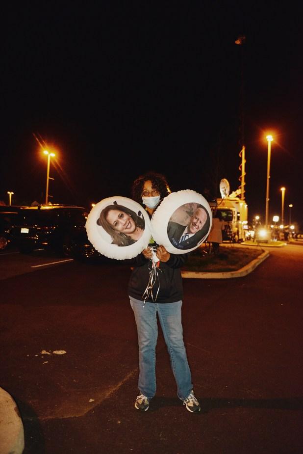 Violetta Smith sostiene globos con retratos de Harris y Biden en un evento al aire libre la noche de las elecciones en Wilmington, Delaware.