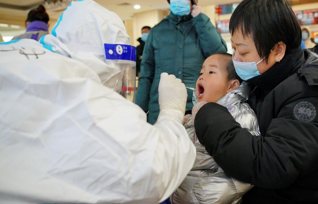A medical worker collects a swab sample from a child a community COVID-19 testing site in Qiaoxi District of Shijiazhuang, capital of north China's Hebei Province, Jan. 12, 2021.