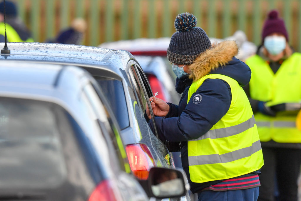 Members of the public receive vaccinations at a drive-through vaccine center in Hyde, near Manchester, U.K., on Friday, Jan. 8, 2021.