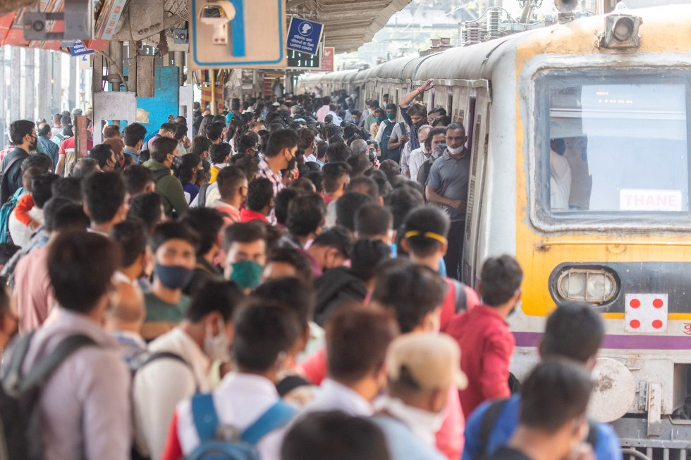 A rush of travellers wait to board a suburban local train at Dadar station, Mumbai, on the first day when local train services started for general public on Feb 1.