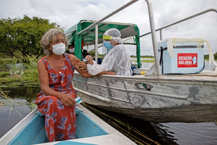 Olga D'arc Pimentel, 72, is vaccinated by a health worker with a dose of the Oxford-AstraZeneca COVID-19 vaccine on the banks of the Rio Negro near Manaus, Brazil, on Feb. 9, 2021.