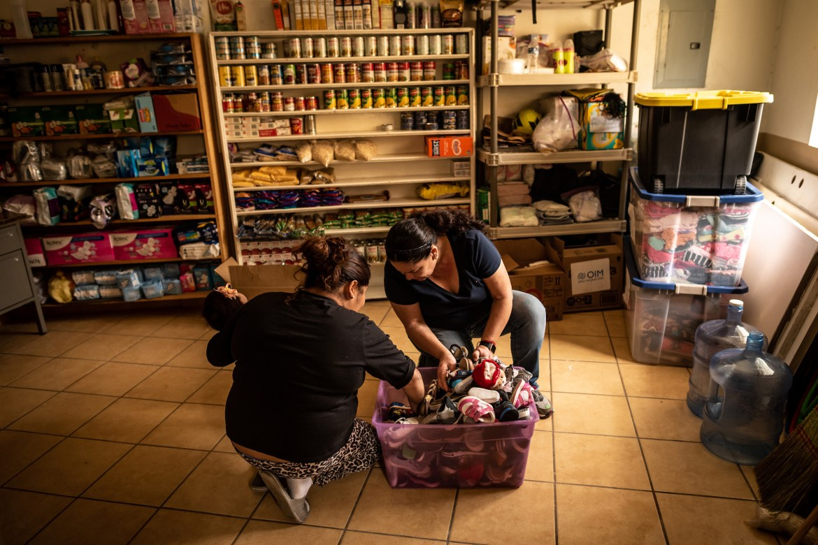 Shelter volunteer Marta Leticia Galarza Gandara, right, helps Isa find shoes for her baby daughter in a box of donations. Isa is an asylum seeker from Honduras, and has been waiting at the border under MPP since September 2019.