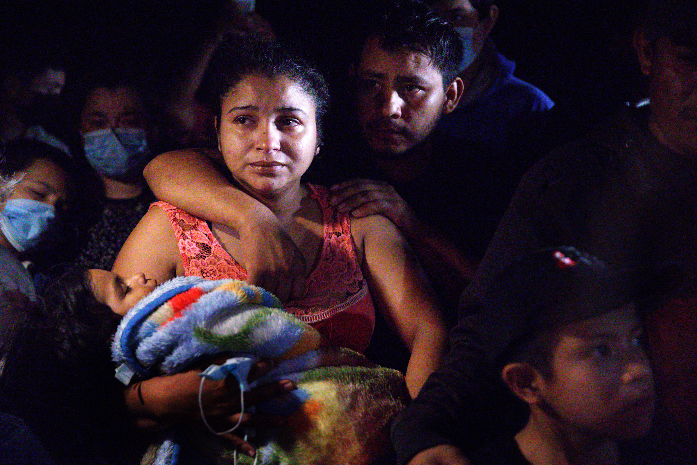 Honduran parents hold their sleeping boy after crossing the Rio Grande from Mexico in Roma, Texas, on April 15, 2021.